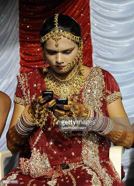 Indian eunuch juggles two cellular telephones during a wedding reception in Ahmedabad on July 12 2009 In the presence of some one hundred eunuchs of...