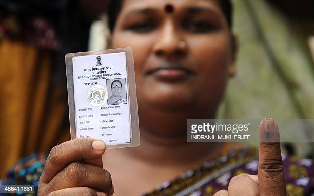 """Indian eunuch Malathi Sharmila Asha shows her inked forefinger and her voter identity card showing her gender as """"other"""" after voting in Mumbai on..."""