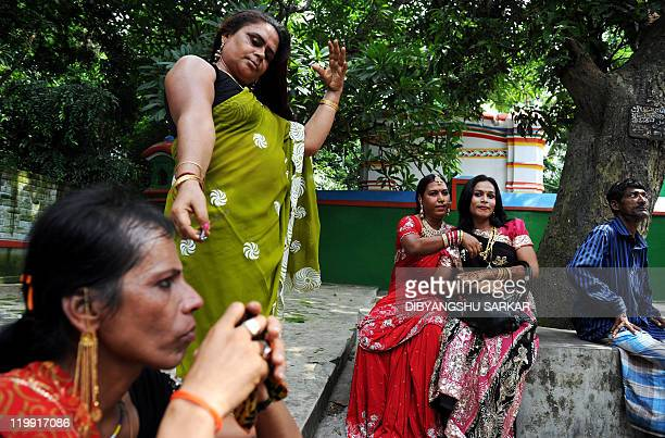 Indian eunuchs paouse under a tree as they wait to offer prayers at an Islamic shrine during a rally in Panduah some 75kms north of Kolkata on July...