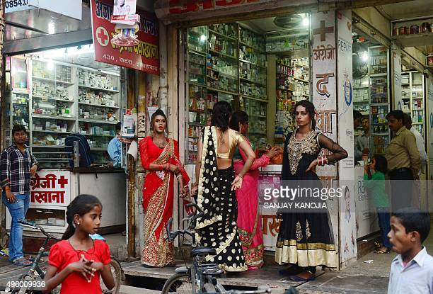 Indian eunuchs stand outside a medical shop as they collect money ahead of the Diwali Festival at a market in Allahabad on November 6 2015 Diwali the...