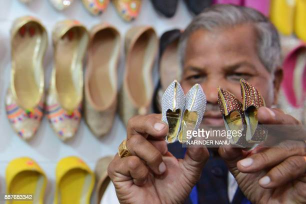 Indian exhibitor Budh Ram holds his handmade miniature shoes known as Punjabi Jutti during The Punjab International Trade Expo PHD 2017 Trade Fair in...