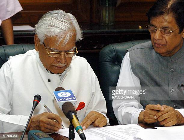 Indian External Affairs Minister Natwar Singh is watched by Minister of State for External Affairs E Ahmed as he signs a list of pilgrims who will...