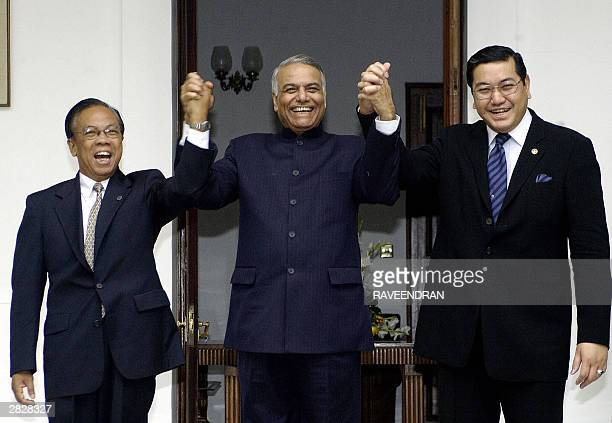 Indian External Affairs Minister Yashwant Sinha Thailand Foreign Minister Surakiart Sathirathai and Myanmar Foreign Minister UWin Aung wave to press...
