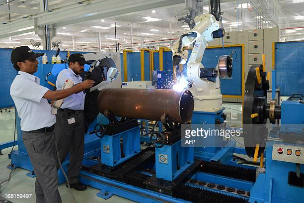 Indian factory employees monitor a robotic welding machine at the Hitachi Home and Life Solutions' air conditioner manufacturing facility near Kadi...