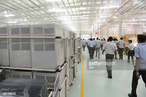 Indian factory employees stop work during their lunch break at the Hitachi Home and Life Solutions' air conditioner manufacturing facility near Kadi...