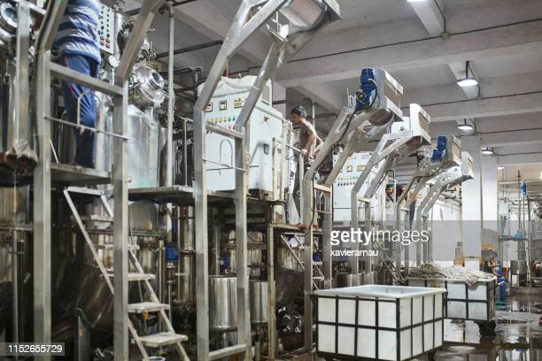indian factory workers operating textile dyeing machinery - maharashtra stock pictures, royalty-free photos & images