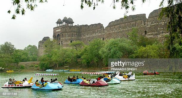 Indian families enjoy boating at Purana Quila during a downpour in New Delhi 26 June 2005 Premonsoon rains in the capital have resulted in citizens...