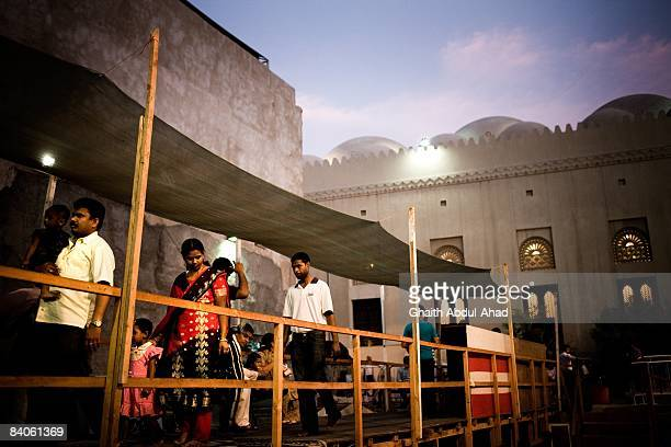 Indian families queue to enter a Shiva temple July 19, 2008 in Old Dubai, United Arab Emirates. Exploitation of hundreds of thousands of underpaid...