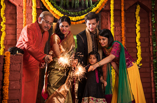 Indian Family celebrating Diwali festival with fire crackers 698710824