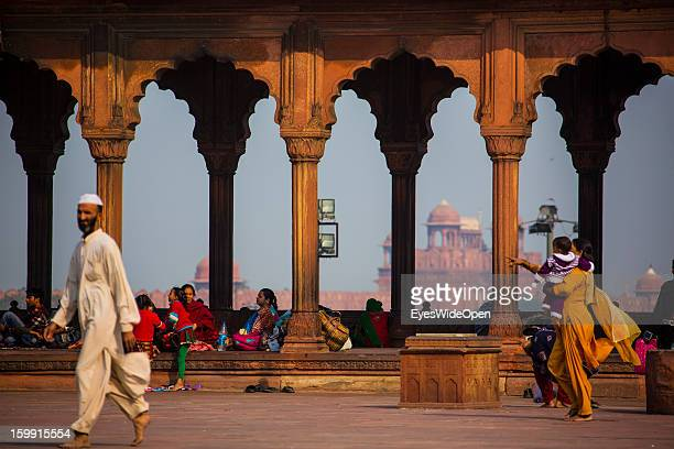 Indian family in the famous Jama Masjid Mosque the largest mosque with a view on the Red Fort in India on December 01 2012 in Old Delhi Delhi India