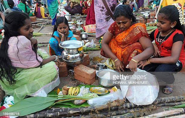 Indian family members watch their mother prepare a special offering during a community function to celebrate Pongal in Mumbai on January 14 2013...