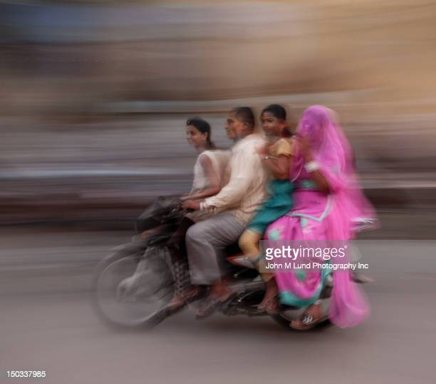 indian family of four crowds together on motorbike in  - four people stock pictures, royalty-free photos & images