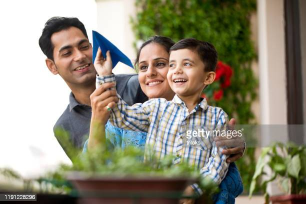 indian family playing with paper airplane - india stock pictures, royalty-free photos & images
