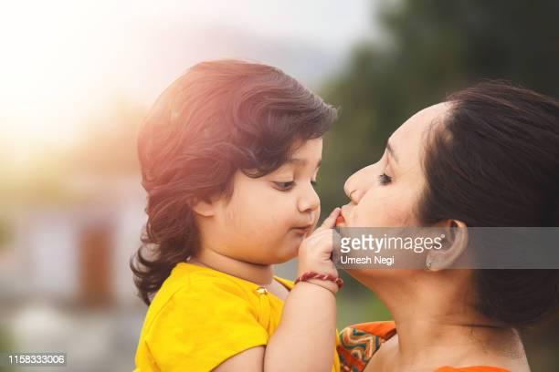 indian family, portrait of indian mother with little baby girl in outdoors - indian girl kissing stock photos and pictures