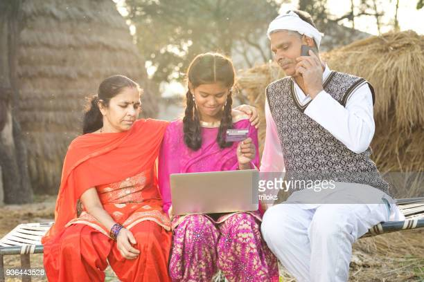 Indian family with laptop and credit card on village bed