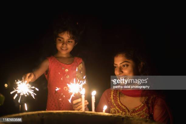indian family,  young mother with her kid girl celebrating diwali/christmas with sparklers - diwali stock pictures, royalty-free photos & images