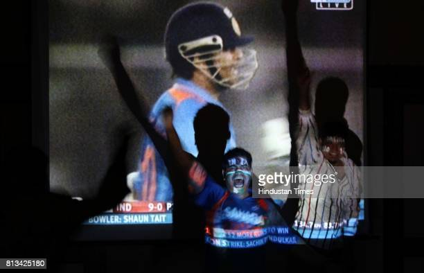 Indian fan celebrates as he watch live telecast of India and Australia match at a restaurant in MUMBAI INDIA Thursday March 24 2011