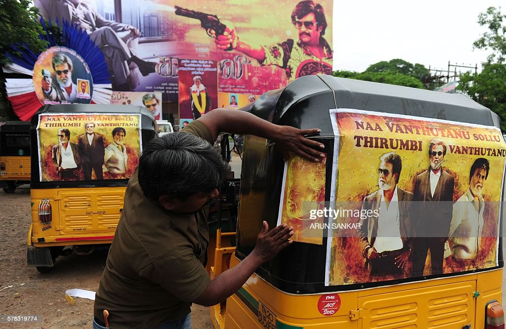 A Indian fan fixes a poster of Indian movie star Rajinikanth on his auto rickshaw in front of a movie theatre, ahead of the release of his Tamil movie 'Kabali', in Chennai on July 21, 2016. As a tradition, fans perform a ritual called paal abhishekam, in which life-size posters of superstar Rajnikanth are bathed in milk before the launch of each of his films. / AFP / ARUN