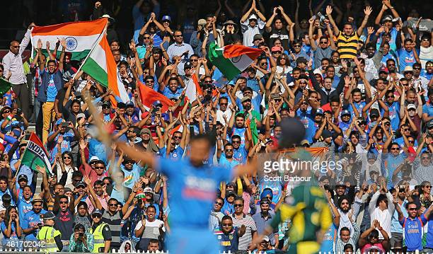 Indian fans in the crowd celebrate as Rohit Sharma of India celebrates as he reaches his century during the One Day International match between...