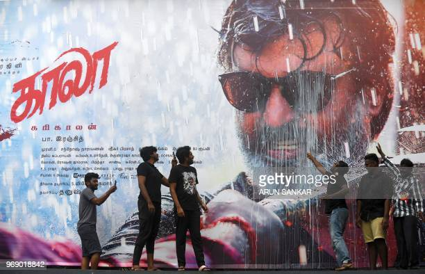 Indian fans pose and take pictures as they celebrate next to a poster of Bollywood star Rajinikanth outside a cinema on the first day of release of...