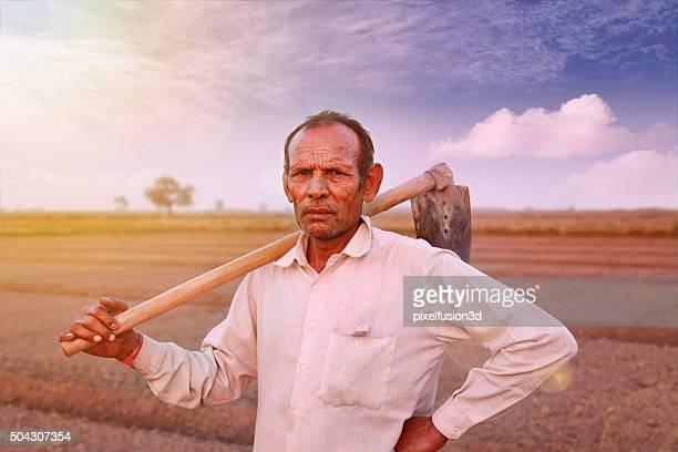 Indian farmer holding hoe on his shoulder