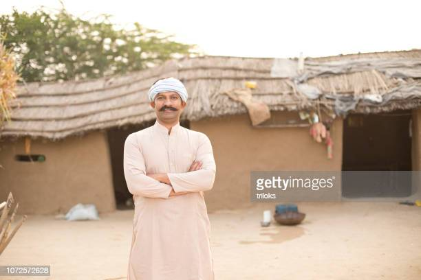 Indian farmer in front of village house