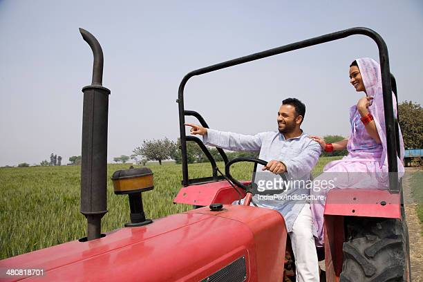 Indian farmer showing something to wife while driving tractor in farm