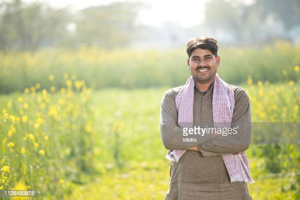 indian farmer standing in agricultural field - indian ethnicity stock pictures, royalty-free photos & images