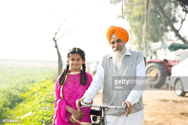 indian farmer with daughter on rural field - punjab india stock pictures, royalty-free photos & images