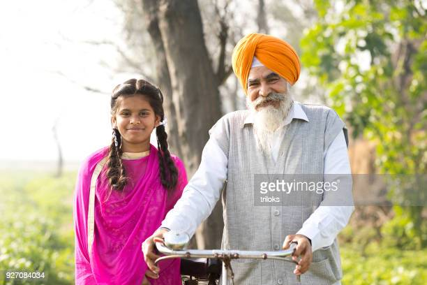 indian farmer with daughter on rural field - punjabi girls images stock photos and pictures