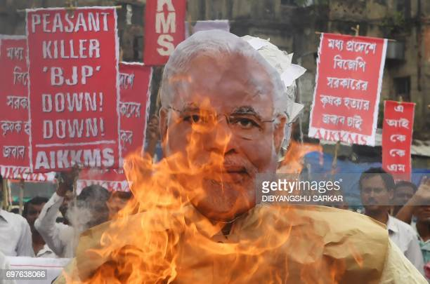 Indian farmers and social activists burn an effigy of Prime Minister Narendra Modi during a protest against the government and over the deaths of...