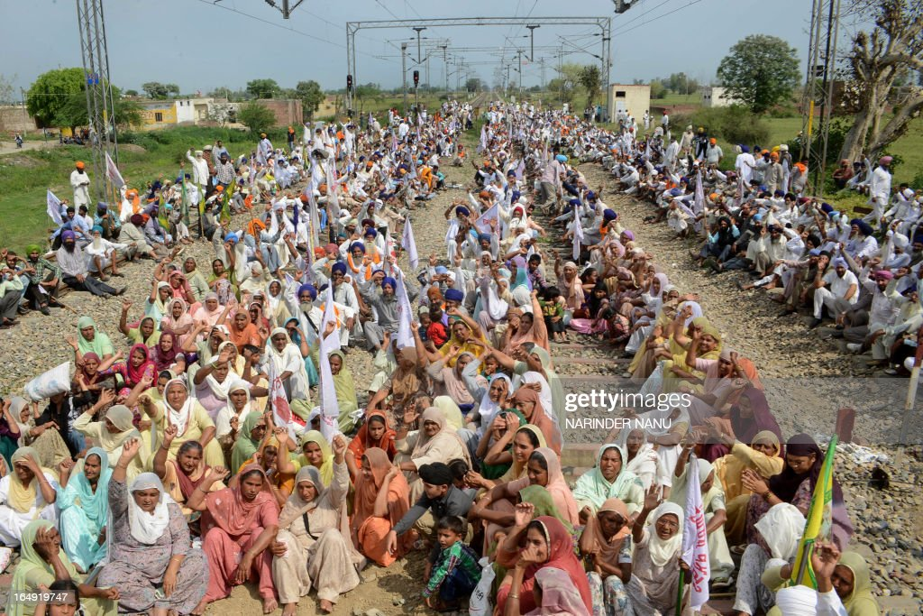 Indian farmers and their wives block the railway tracks as they pay tribute to farmer Angrej Singh Bakipur who died during police fire at a railway...