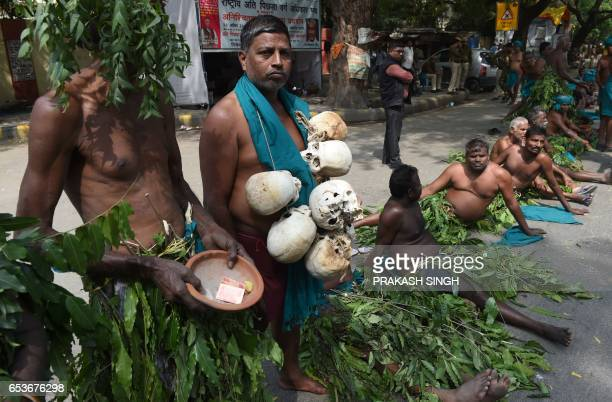 Indian farmers from the southern state of Tamil Nadu wear tree leaves and hold symbolic 'skulls' as they take part in a protest in New Delhi on March...