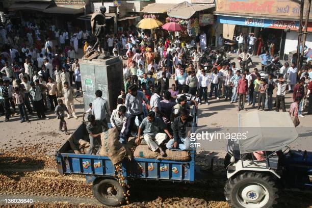Indian farmers including potato growers merchants and cold storage owners participate in a protest by dumping potatoes and blocking a highway in...