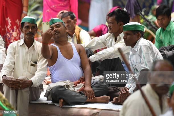 Indian farmers of the Bhartiya Kisan Union take selfie while listening to a speech during a protest against Prime Minister Narendra Modi and the...