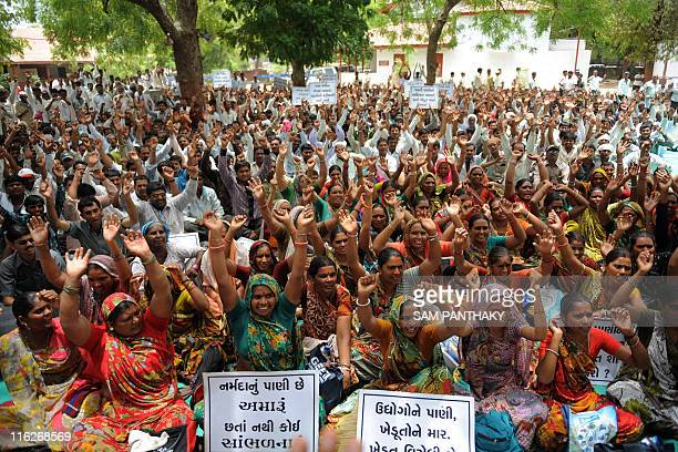 Indian farmers raise their arms during a protest against water supply in Ahmedabad on June 15 2011 The farmers were protesting against the lack of...