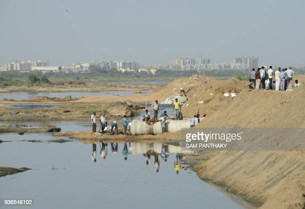 Indian farmers repair a canal to channel treated water from the Sabarmati River to the Fatehwadi Canal near Fatehwadi village some 20 kms from...