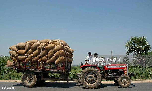 Indian farmers transport a load of their harvested paddy on a tractor to the rice mill at Miryalaguda Mandal of Nalgonda District which is some 150...