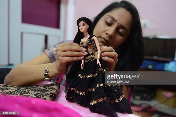 Indian fashion designer Hima Sailaja Theerdhala puts an outfit onto her selfdesigned Indian fashion doll 'Kiyaa' at her Shel design studio in...