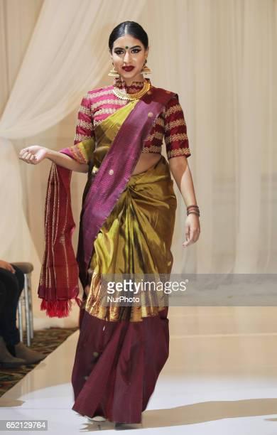 Indian fashion model wearing an elegant and ornate Kanchipuram saree from the 'Lemon Chiffon Fashion Collection' during a South Asian bridal fashion...