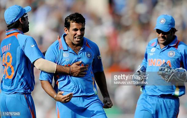 Indian fastbowler Zaheer Khan celebrates with teammate Virat Kohli and captain Mahendra Singh Dhoni after taking the wicket of unseen Australian...