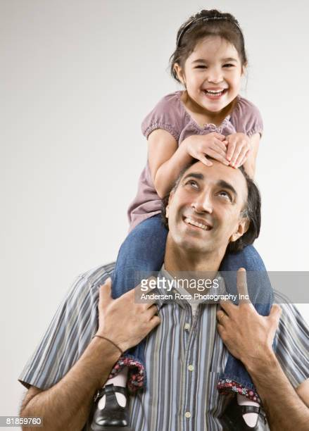 Indian father holding daughter on shoulders