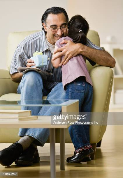 Indian father holding gift and hugging daughter