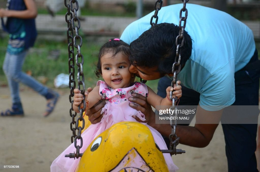 Indian father Kuldeep kisses his daughter Vanshika as she sits on a swing at a park in Amritsar on June 17 on Father`s Day a day observed in many...