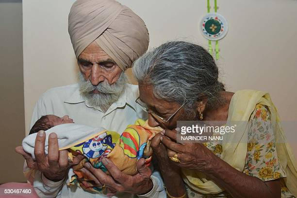 TOPSHOT Indian father Mohinder Singh Gill and his wife Daljinder Kaur pose for a photograph as they hold their newborn baby boy Arman at their home...