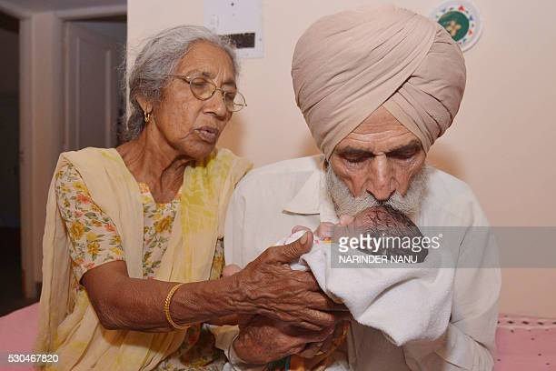 Indian father Mohinder Singh Gill and his wife Daljinder Kaur pose for a photograph as they hold their newborn baby boy Arman at their home in...
