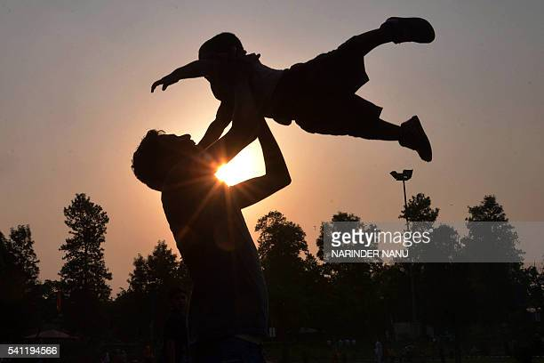 Indian father Shailesh throws up his son Harish at a park in Amritsar on June 19 on Father's Day a day observed in many countries to celebrate...