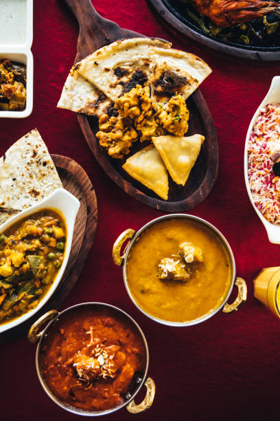 Indian feast with butter chicken, chicken tandoori, lamb curry, vegetable curry, samosas, pakoras, bhajis, naan bread and basmati rice on a table. Nor