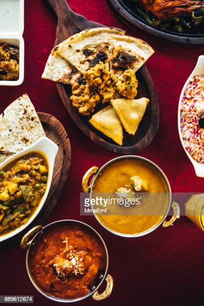 indian feast with butter chicken, chicken tandoori, lamb curry, vegetable curry, samosas, pakoras, bhajis, naan bread and basmati rice on a table. north indian food - samosa stock photos and pictures