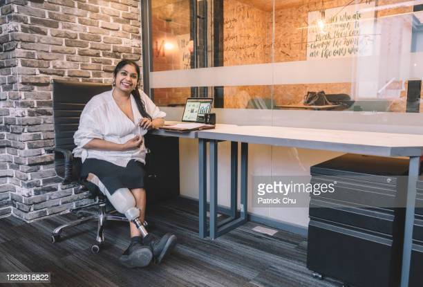 indian female amputee businesswomen working at office - leanincollection stock pictures, royalty-free photos & images
